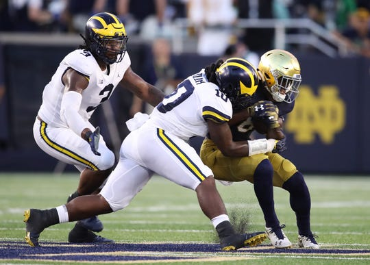 Michigan's Devin Bush tackles Notre  Dame's Jafar Armstrong in the first quarter at Notre Dame Stadium on Sept. 1, 2018 in South Bend, Ind.