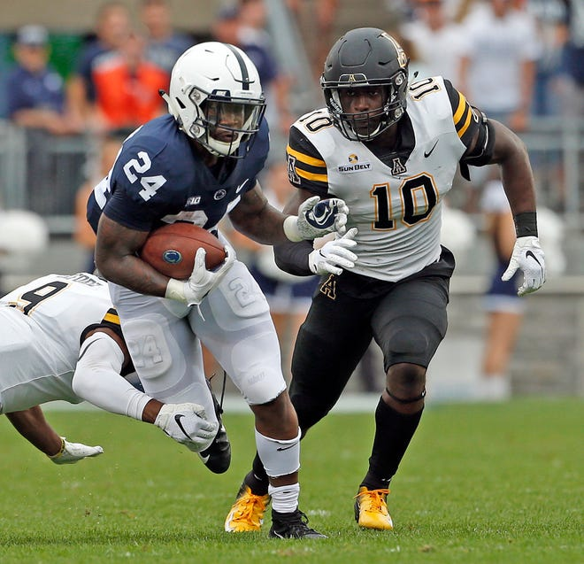 Penn State's Miles Sanders (24) evades a tackle by Appalachian State's Austin Exford (9) and Tim Frizzell (10) during the first half on Saturday.