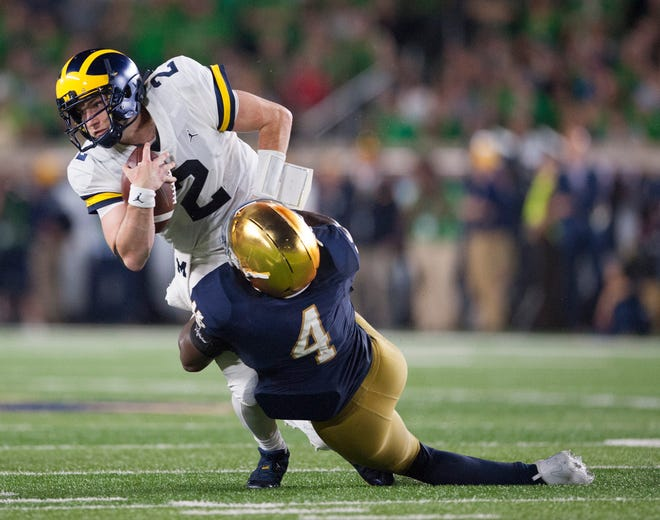 Michigan quarterback Shea Patterson is tackled by Notre Dame linebacker Te'von Coney (4) in the fourth quarter.