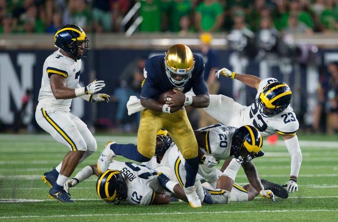 Notre Dame quarterback Brandon Wimbush leaves a host of Michigan defenders in his wake, including linebacker Khaleke Hudson (7), Josh Ross (12), Brad Hawkins (20) and Tyree Kinnel (23).