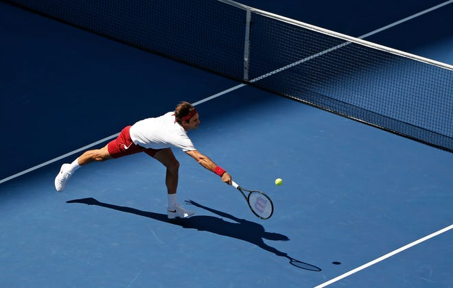 Roger Federer returns a shot to Nick Kyrgios during the third round of the U.S. Open on Saturday.