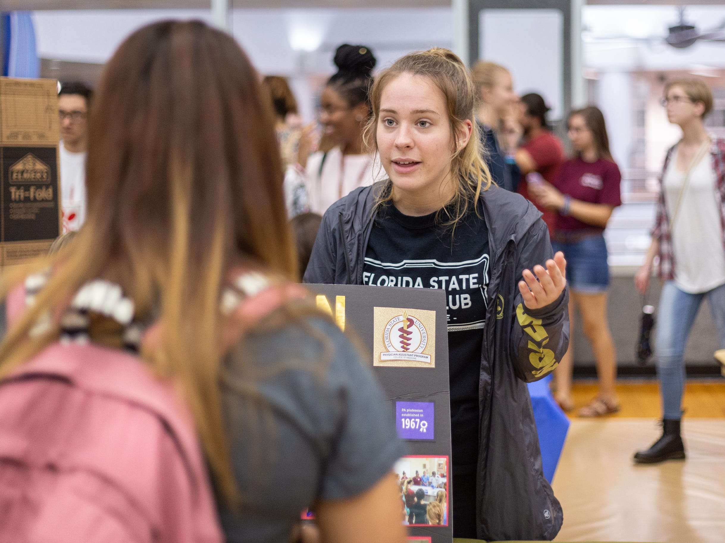 Monica Rowe (right), shares the invaluable experience she gains from her membership in FSU's pre-Physician Assistant Club on Tuesday at FSU's Involvement Fair in the Tully Gymnasium, Tallahassee, FL.