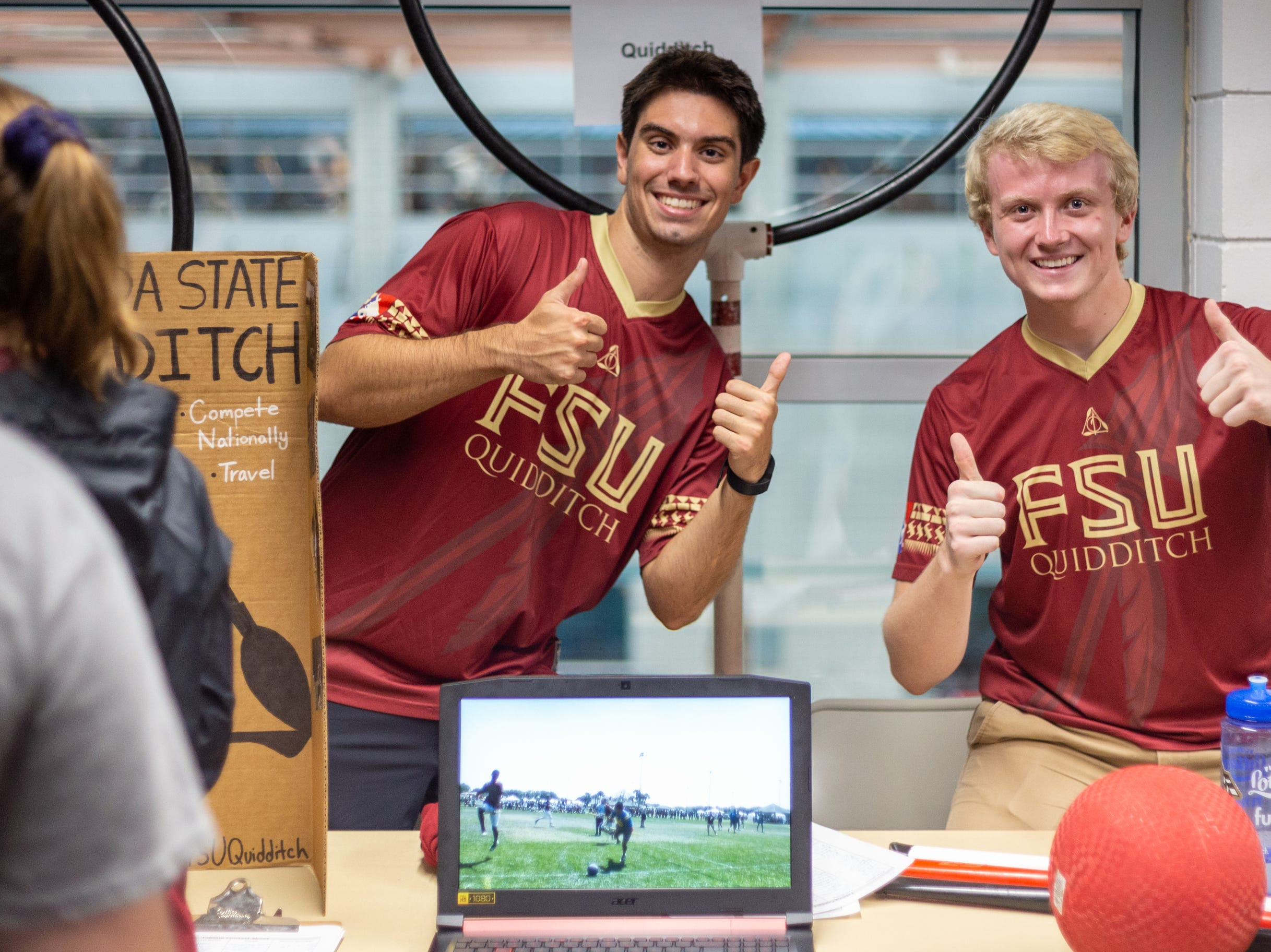 FSU Quidditch club members, James Pulson (right) and Andrew Ibarra (left), give a double thumbs up for club sports on Tuesday at FSU's Involvement Fair in the Leach Center.