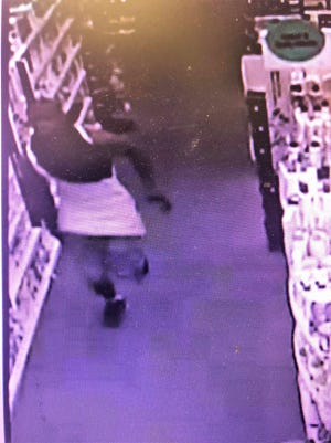 In this photo provided by the Greenville County Sheriff's Office, one of two men involved in an armed robbery at about 3:45 a.m. Sunday, Sept. 2, 2018, at the CVS drugstore on Fairview Road in Greenville is captured on camera during the incident.