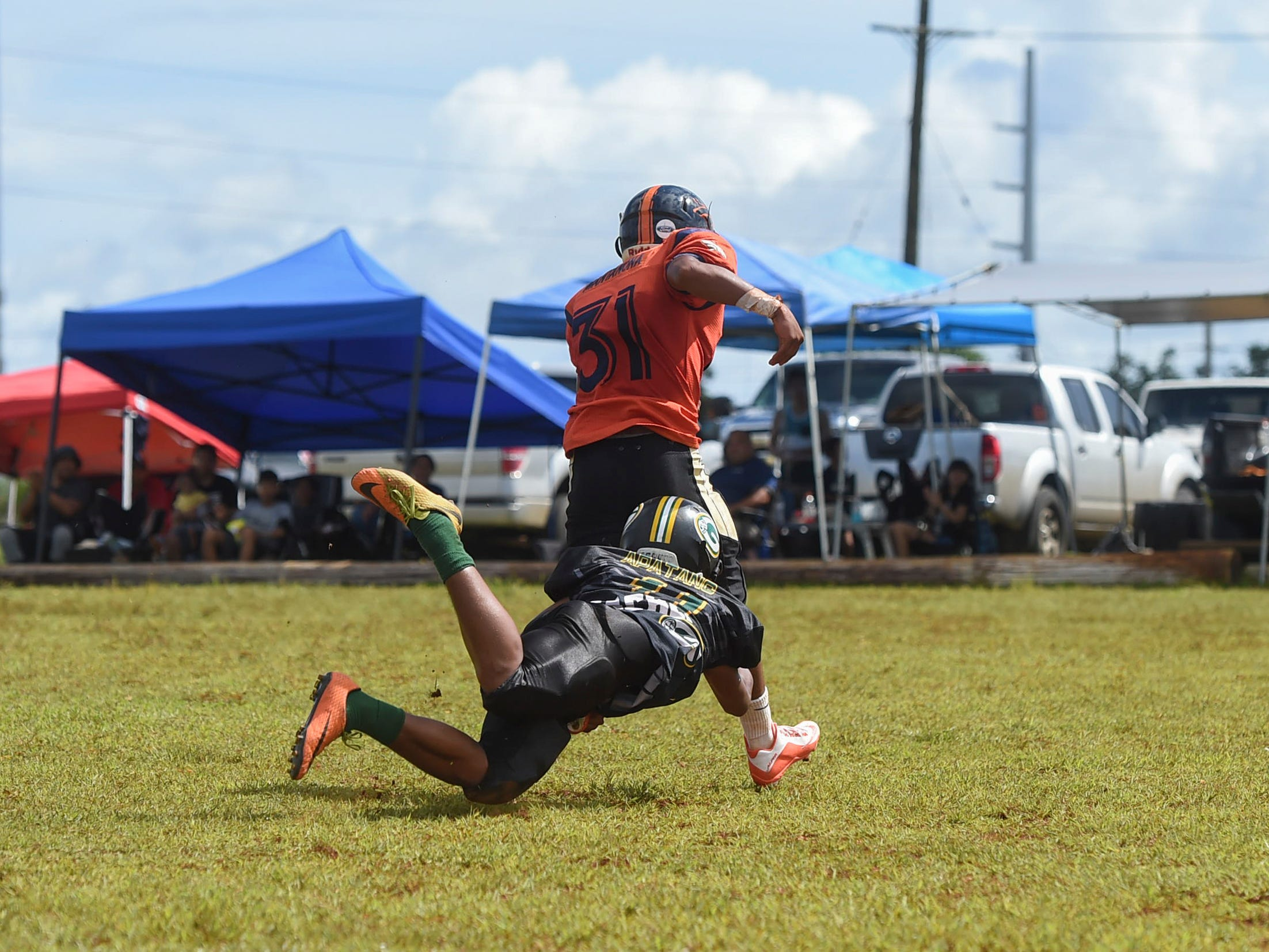 Guam Packers player Dreyvin Apatang (11) dives for a tackle on the Broncos' Francisco Mantanona (31) during a Guam National Youth Football Federation Matua division game at the Mikkel Tan I. Vy Field in Tiyan, Sept. 2, 2018.