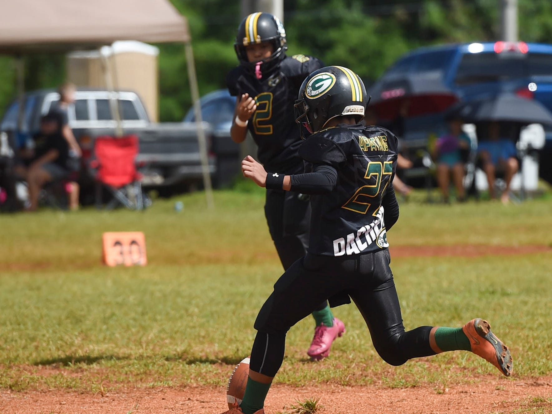 Guam Packers player Austin Apatang (27) kicks the opening kickoff against the Cinnabon Island Brocons in their Guam National Youth Football Federation Matua division game at the Mikkel Tan I. Vy Field on Sept. 2, 2018.