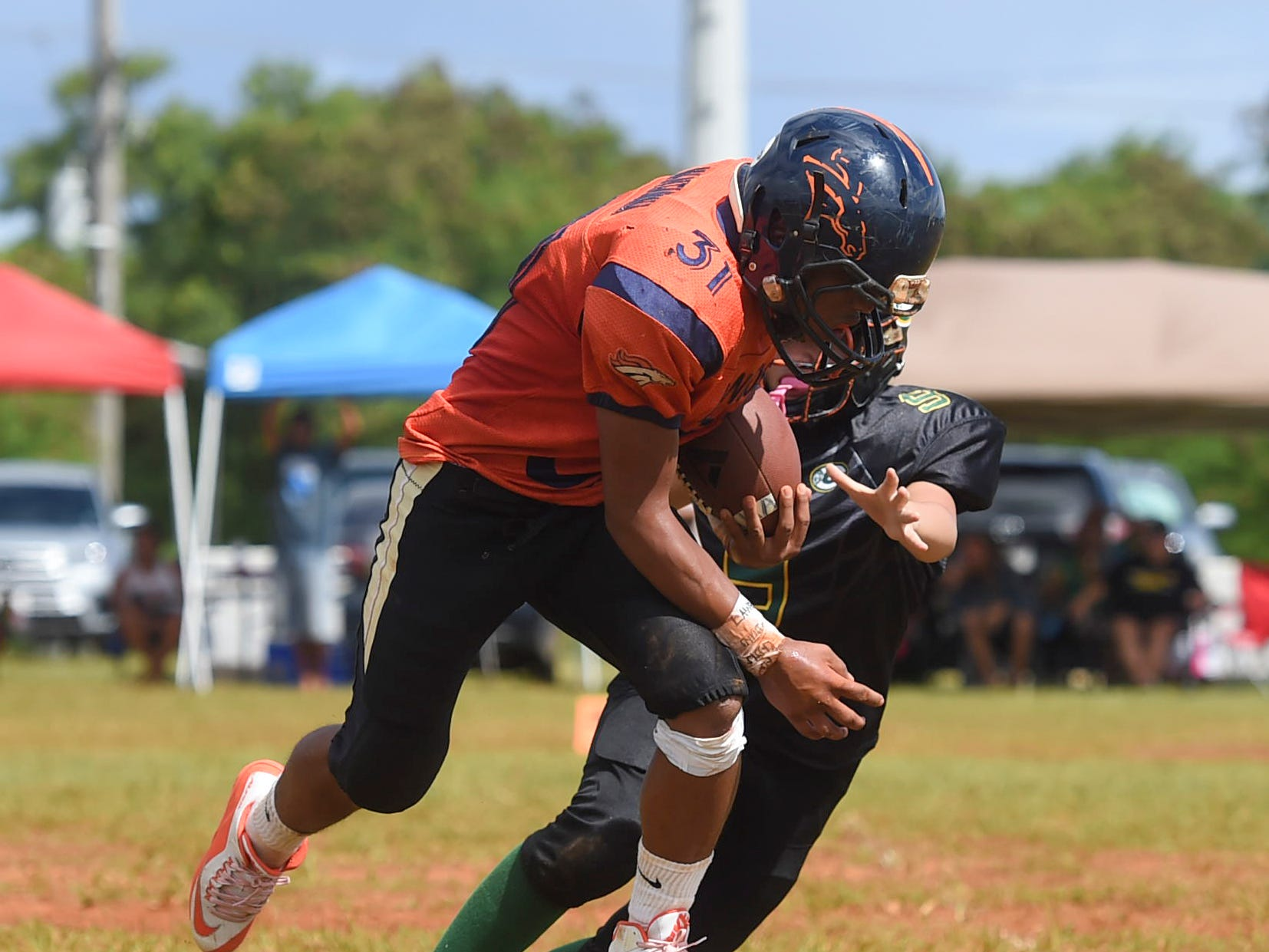 Cinnabon Island Broncos' Francisco Mantanona (31) makes an athletic move to elude a Guam Packers player during their Guam National Youth Football Federation Matua division game at the Mikkel Tan I. Vy Field in Tiyan on Sept. 2, 2018.during their Guam National Youth Football Federation Matua division game at the Mikkel Tan I. Vy Field in Tiyan on Sept. 2, 2018.
