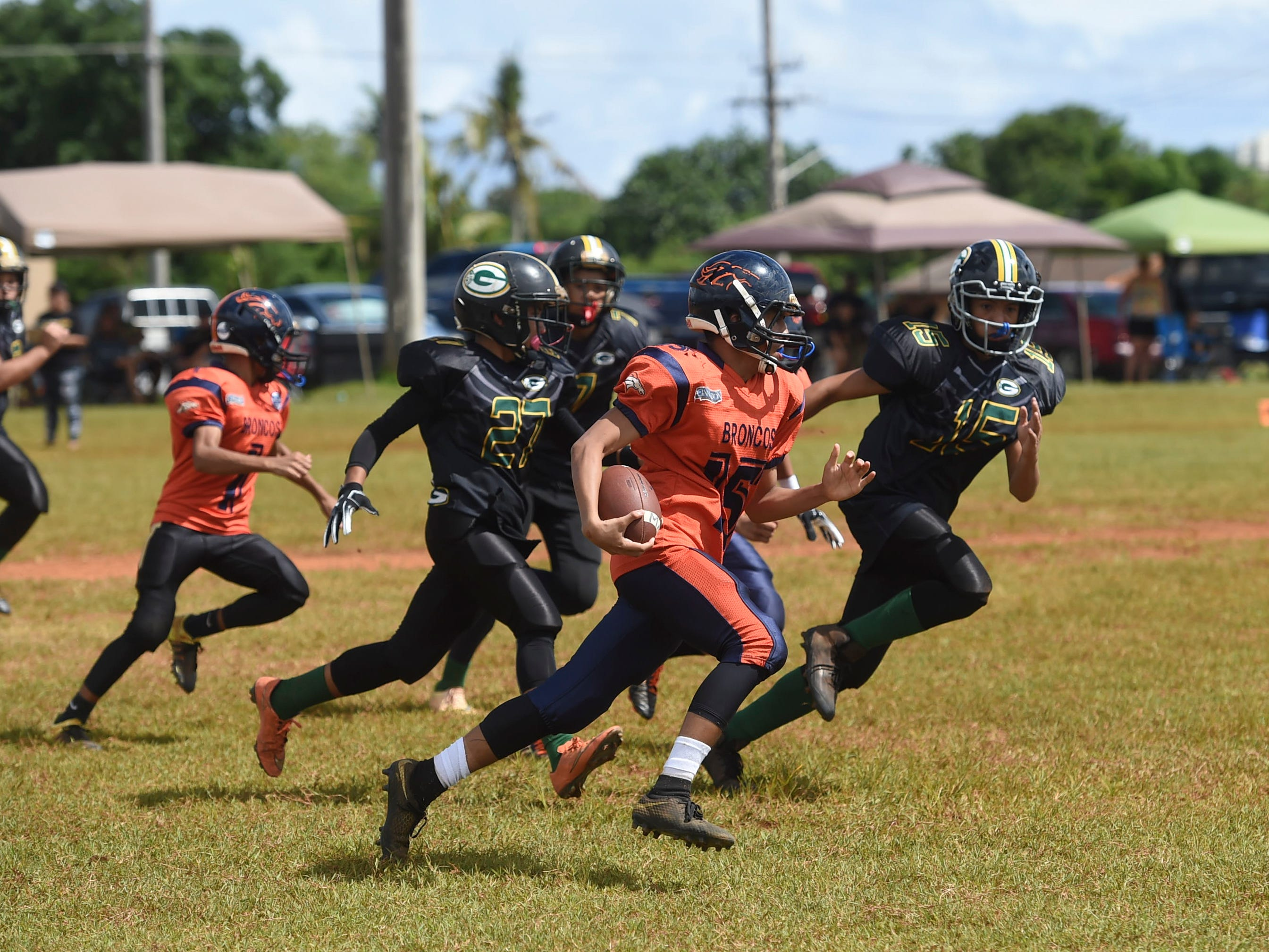Cinnabon Island Broncos player Ipo Aguon Indalecio (15) runs the ball against the Guam Packers during their Guam National Youth Football Federation Matua division game at the Mikkel Tan I. Vy Field in Tiyan on Sept. 2, 2018.