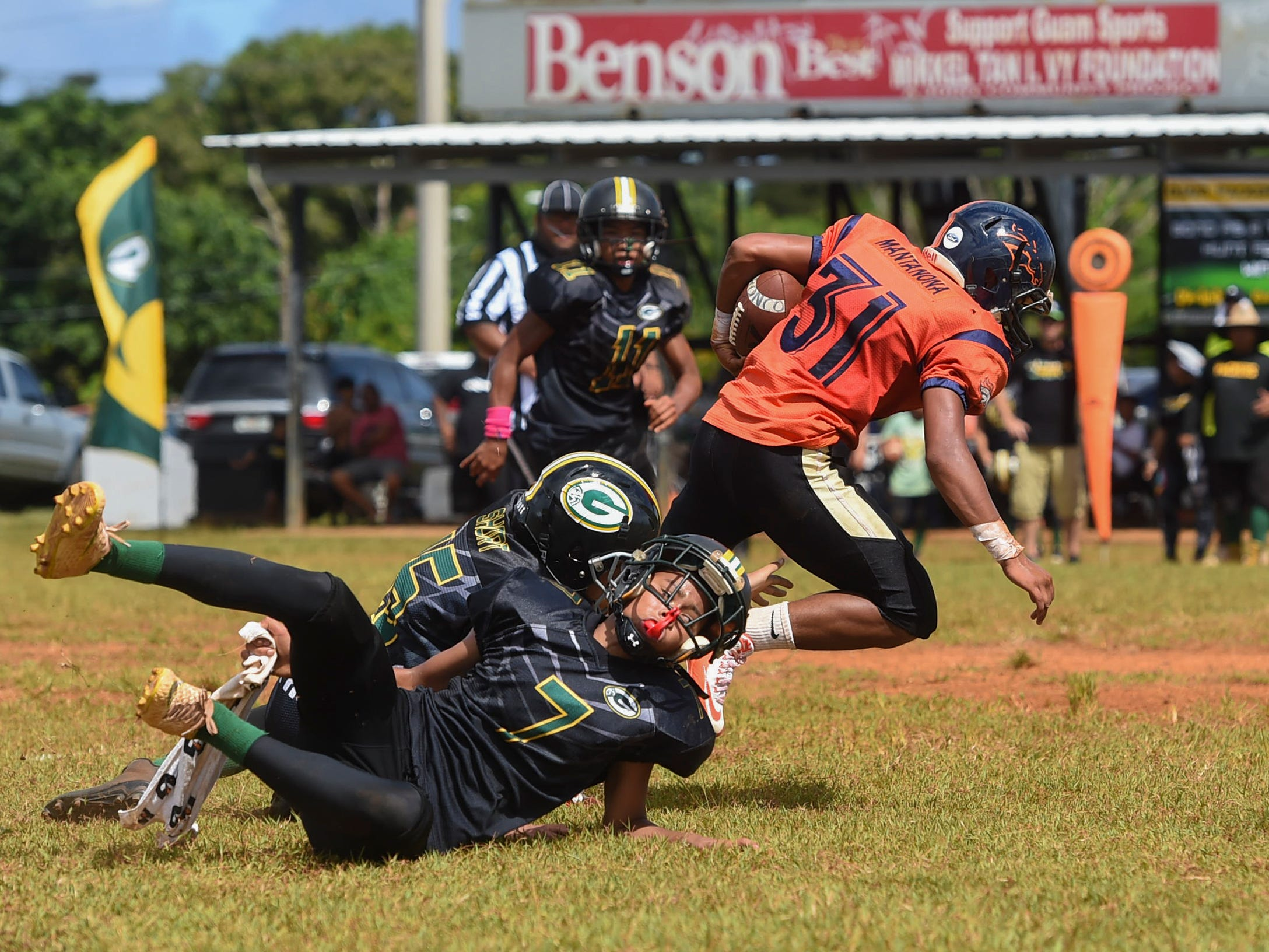 Cinnabon Island Broncos player Francisco Mantanona (31) breaks free from Guam Packers defensive players during their Guam National Youth Football Federation Matua division game at the Mikkel Tan I. Vy Field in Tiyan on Sept. 2, 2018.