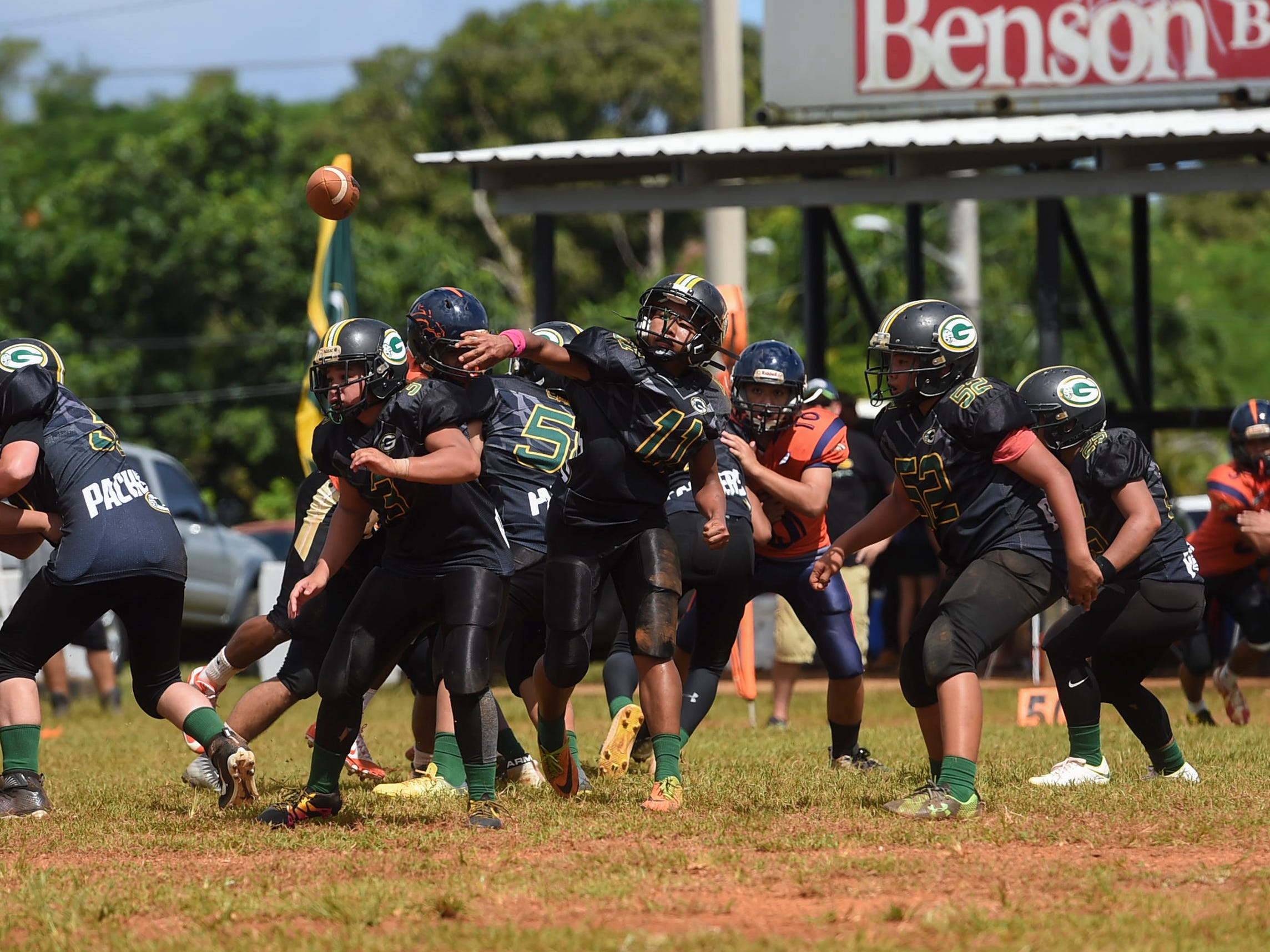 Guam Packers quarterback Dreyvin Apatang (11) passes out of the pocket during a Guam National Youth Football Federation Matua division game at the Mikkel Tan I. Vy Field in Tiyan on Sept. 2, 2018.