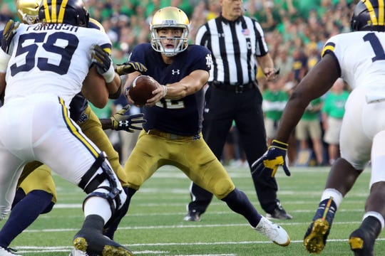 Notre Dame Fighting Irish quarterback Ian Book (12) hands the ball off against the Michigan Wolverines. Notre Dame defeats the Michigan Wolverines 24-17 Notre Dame Stadium in South Bend, Ind.,on Saturday, September 1, 2018