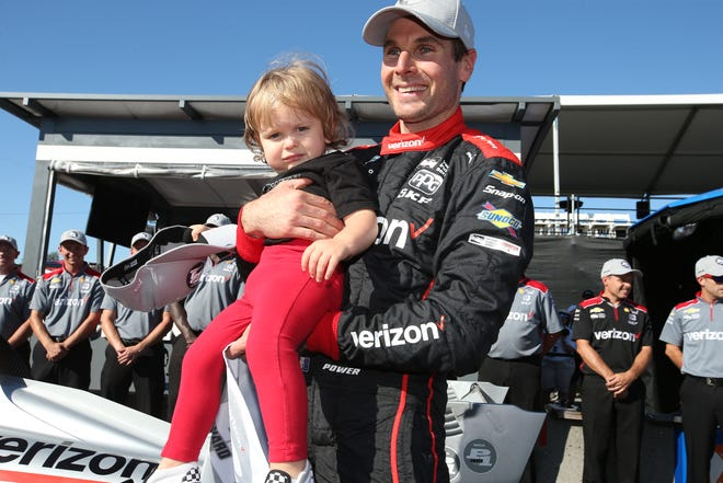 Will Power celebrates with his son, Beau, on pit lane after winning the pole position for the Grand Prix of Portland Saturday at Portland International Raceway.