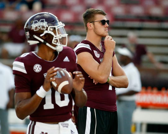 Mississippi State quarterback Nick Fitzgerald, rear, watches as starting quarterback Keytaon Thompson (10) passes during warmups prior to their NCAA college football game against Stephen F. Austin on Saturday, Sept. 1, 2018, in Starkville, Miss. Fitzgerald, who was scheduled to start, was serving a one-game suspension for violation of team rules. (AP Photo/Rogelio V. Solis)