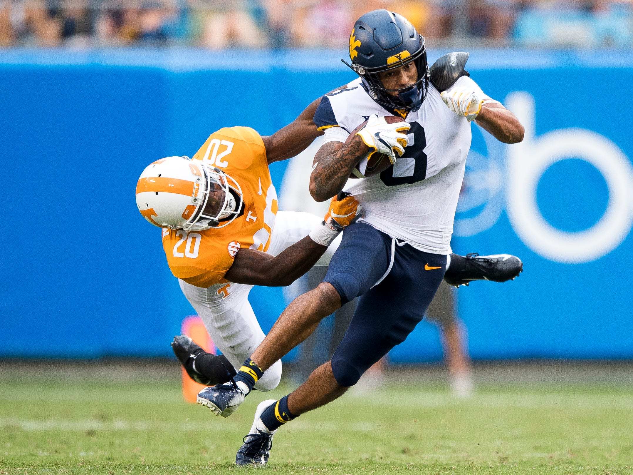 West Virginia wide receiver Marcus Simms (8) escapes a tackle by Tennessee defensive back Bryce Thompson (20) during the Tennessee Volunteers' game against West Virginia in the Belk College Kickoff at Bank of America Stadium in Charlotte, N.C., on Saturday, Sept. 1, 2018.