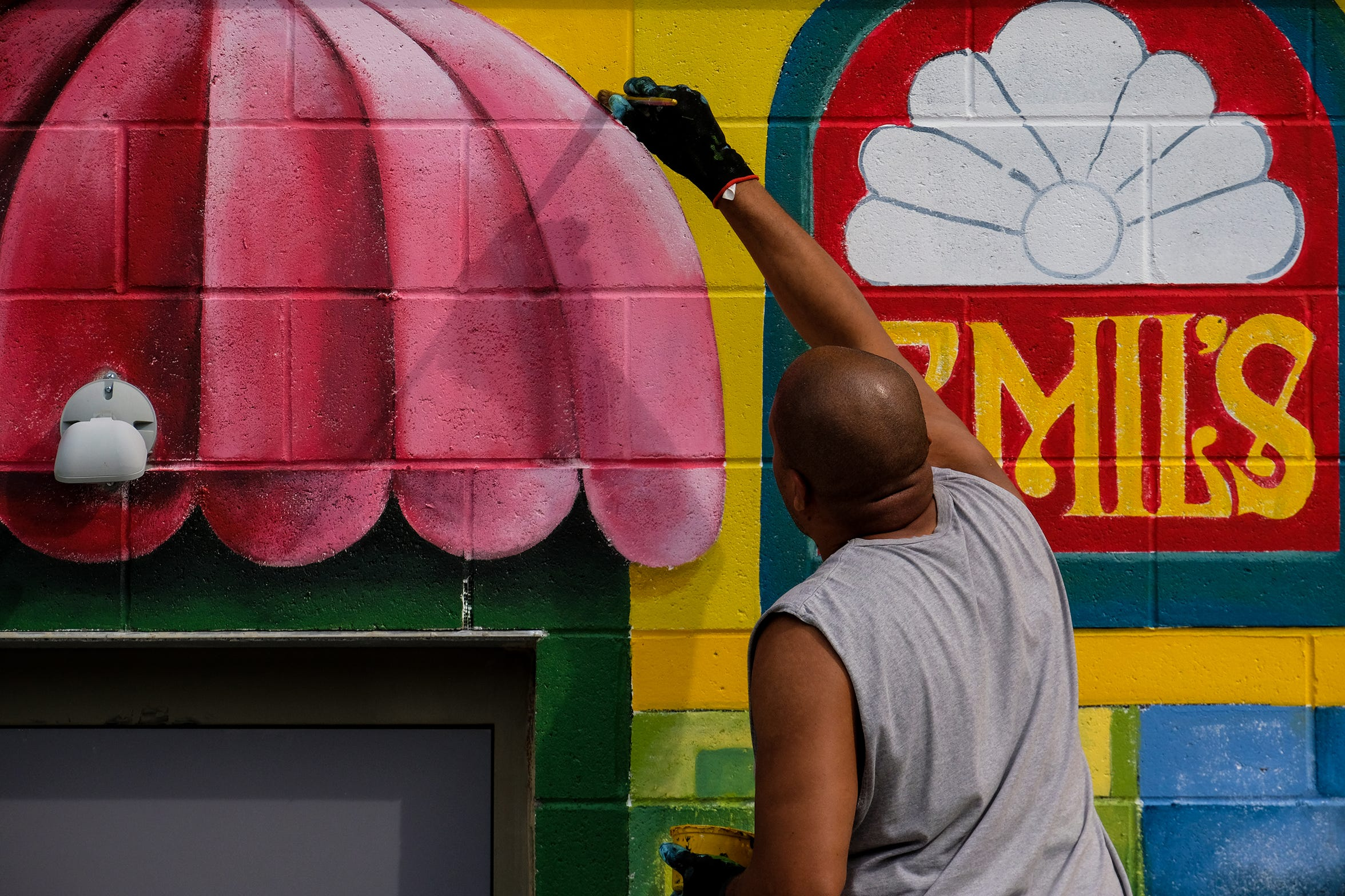 Brian Whitfield works on one of several murals he is creating on the back of the Venue on Michigan Avenue and Clemens Street in Lansing. He is showing a history of Lansing's Eastside in his work.
