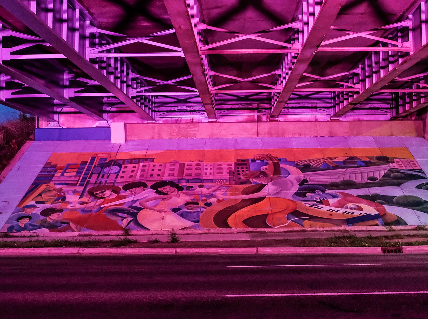"""Under the Bridge"" murals by Brian Whitfield are lit up at night."