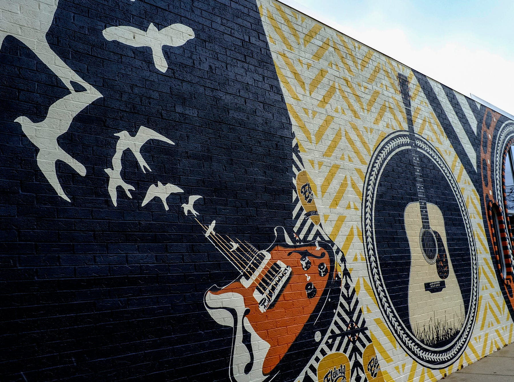 A 68 foot mural by Jennifer Springman is displayed on the wall of Elderly Instruments at 1100 N. Washington Avenue in Lansing's Old Town.