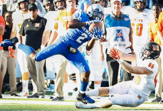 Memphis defender T.J. Carter (left) returns an interception for a touchdown in front of Mercer tight end Chris Ellington (right) during their college football game at The Liberty Bowl Memorial Stadium in Memphis, Tenn., Saturday, September 1, 2018.