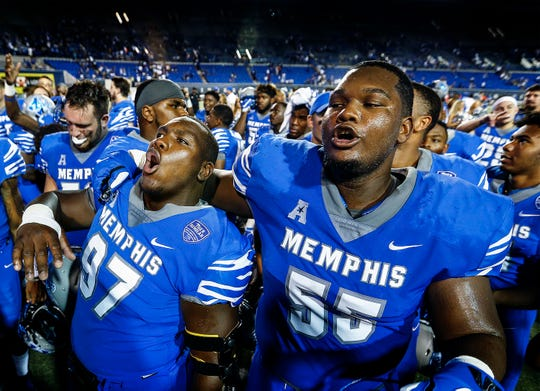 Memphis teammates Emmanuel Cooper, left, and Mikhail Hill celebrate after defeating Mercer 66-14 at the Liberty Bowl Memorial Stadium in Memphis on Sept. 1, 2018.