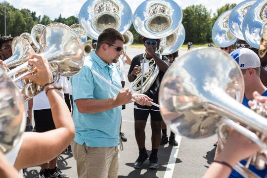 Collierville High School director of bands James Barnes gathers marching band members during practice Aug. 31. The band will host the Tournament of Champions, the school's first marching band competition, at the new football stadium Sept. 29.