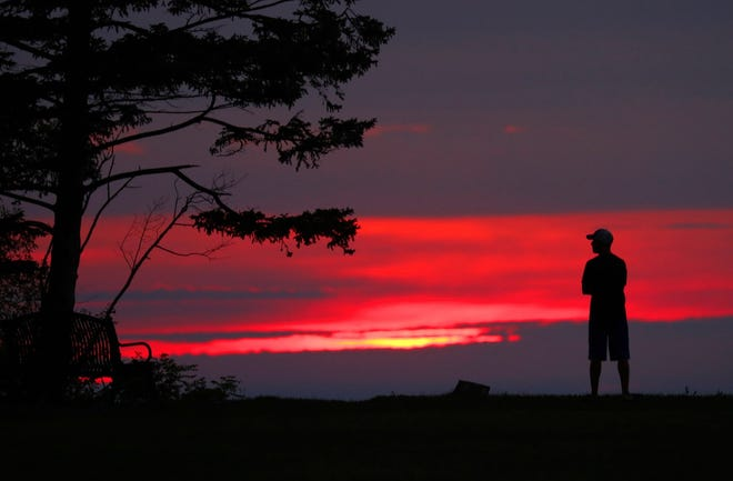 Mark Behnke, of Thiensville, watches the sunrise over Lake Michigan at Virmond Park on North Lake Shore Drive in Mequon on Saturday.