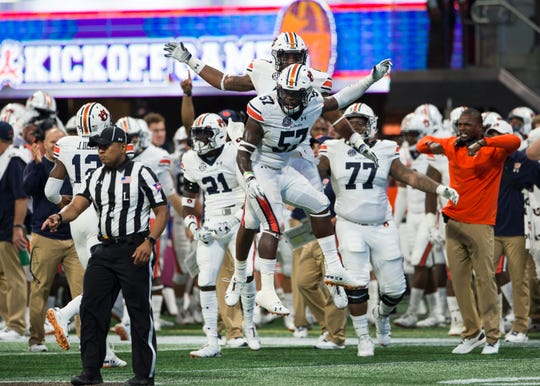 Auburn's Deshaun Davis (57) and Darrell Williams (49) celebrate after Washington misses a field goal at Mercedes-Benz Stadium in Atlanta, Ga., on Saturday, Sept. 1, 2018. Auburn defeated Washington 21-16 in the Chick-fil-a Kickoff Game.