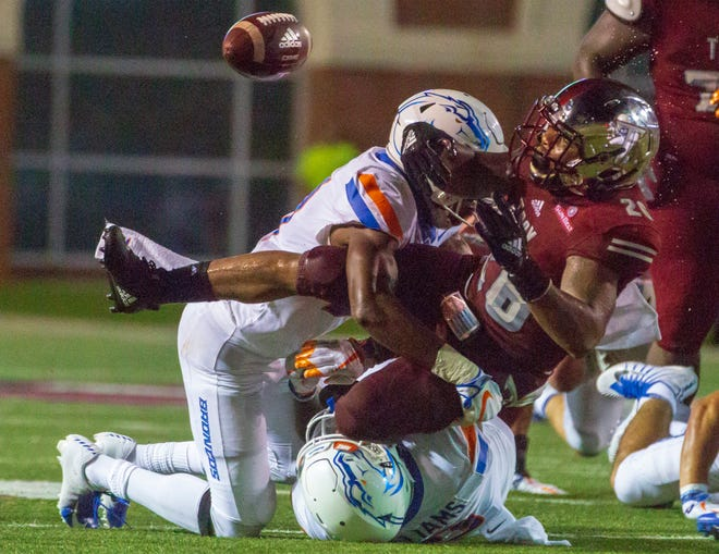 Troy's B.J. Smith loses the ball after Boise State's Tyreque Jones takes him down in a tackle.