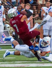 Troy's Kaleb Barker is brought down by a Boise State player during the first half.
