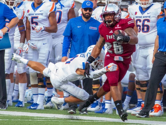 Boise State's DeAndre Pierce dives for a tackle on Troy's B.J. Smith during the first half.