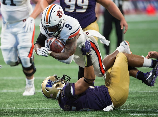 Auburn's Kam Martin (9) barrels through Washington's DJ Beavers (15) at Mercedes-Benz Stadium in Atlanta, Ga., on Saturday, Sept. 1, 2018. Auburn defeated Washington 21-16 in the Chick-fil-a Kickoff Game.