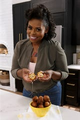 "Jamika Pessoa poses with her Crab Stuffed Hush Puppies, or Crush Puppies, as seen on ""Let's Eat."""