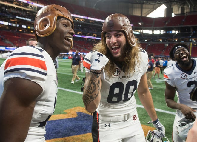 Auburn's Marquis McClain (17) and Sal Cannella (80) joke around with the old leather helmet trophy at Mercedes-Benz Stadium in Atlanta, Ga., on Saturday, Sept. 1, 2018. Auburn defeated Washington 21-16 in the Chick-fil-a Kickoff Game.