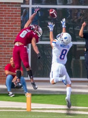 Troy's Marcus Jones bends over backwards to catch a high pass as Boise State's Sean Modster tries for the same.