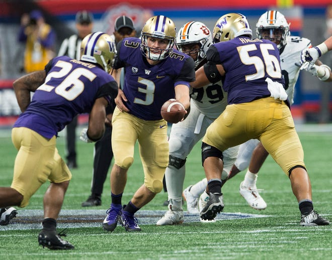 Washington's Jake Browning (3) hands the ball off to Washington's Salvon Ahmed (26) at Mercedes-Benz Stadium in Atlanta, Ga., on Saturday, Sept. 1, 2018. Auburn defeated Washington 21-16 in the Chick-fil-a Kickoff Game.
