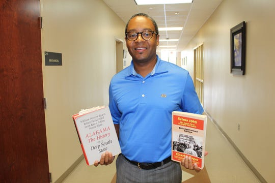 Wallace Community College official Johnny Moss III holds two books on Alabama's role during America's civil rights era. Alvin Benn/Special to the Advertiser