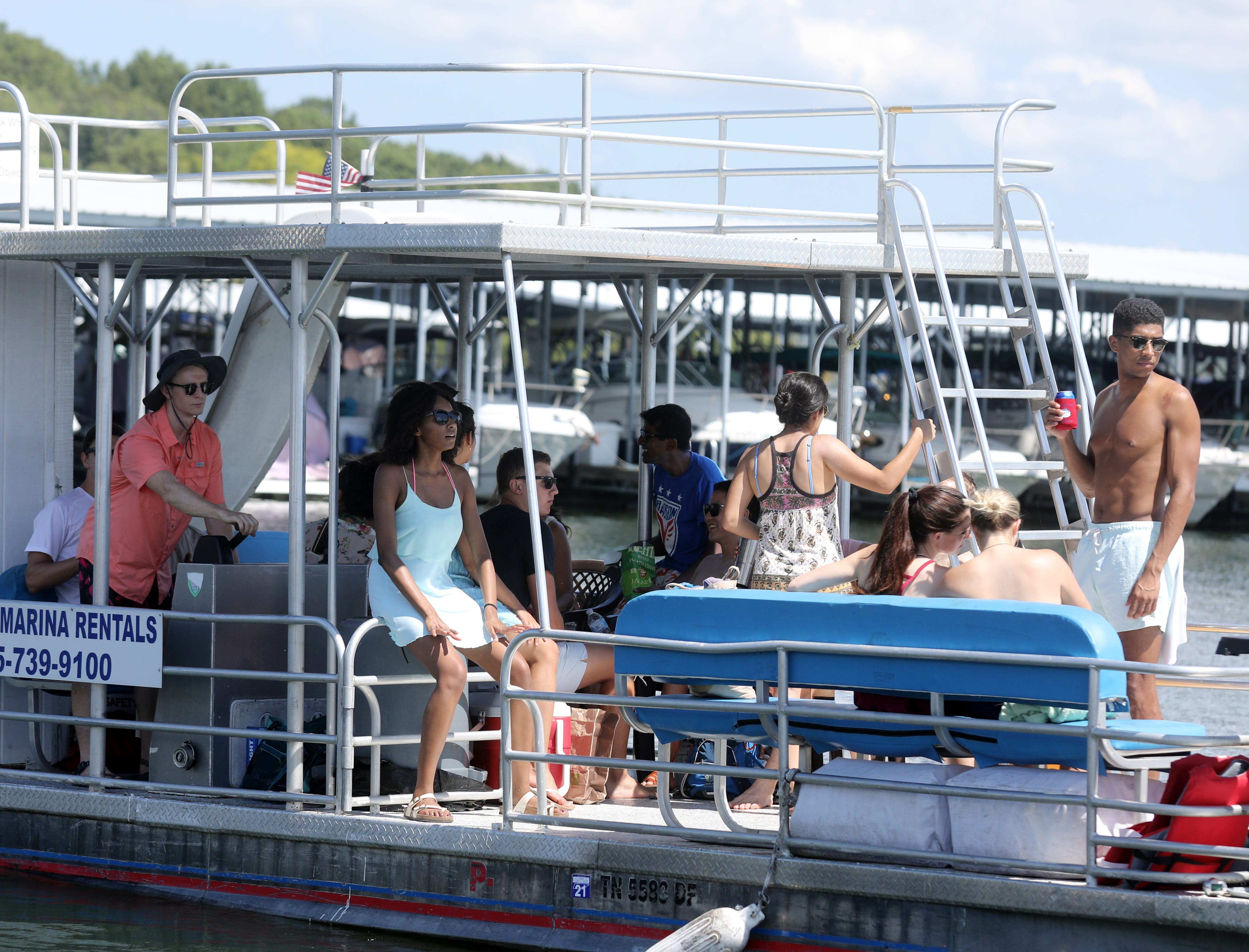 Jeremy Hatcher, far left, drives a boat with his friends at Elm Hill Marina on Percy Priest Lake Sunday September 2, 2018.