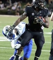 Vanderbilt running back Ke'Shawn Vaughn (5) tries to escape the grasp of MTSU safety Kylan Stribling.