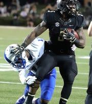 Vanderbilt running back Ke'Shawn Vaughn (5) tries to escape the grasp of MTSU safety Kylan Stribling.