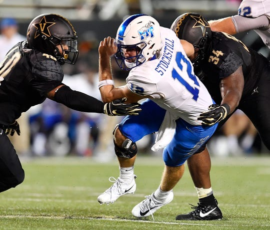 Middle Tennessee quarterback Brent Stockstill (12) is stopped by Vanderbilt linebacker Jordan Griffin (40) and defensive lineman Dare Odeyingbo (34) as he tries to rush with the ball during the first half at Vanderbilt Stadium Saturday, Sept. 1, 2018, in Nashville, Tenn.