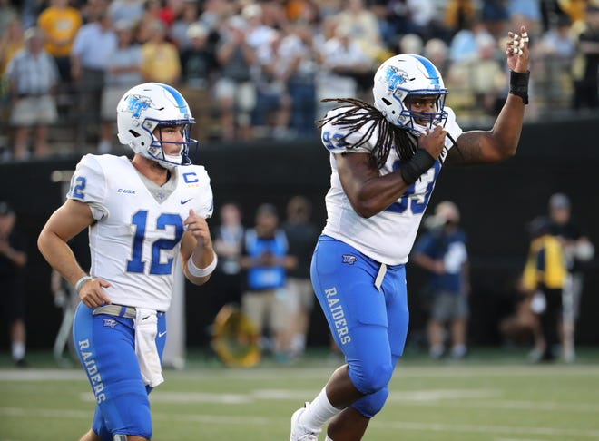 Middle Tennessee quarterback Brent Stockstill (12) and defensive tackle Malik Manciel (93) head back to the team after the coin flip before the game at Vanderbilt Stadium Saturday, Sept. 1, 2018, in Nashville, Tenn.