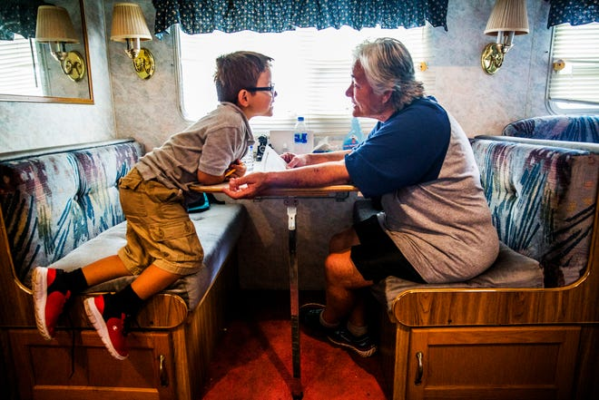 Debbie Coe, 62, helps her great-nephew Casey Soto, 6, with his homework in the RV they share in Immokalee on Wednesday, Aug. 22, 2018.