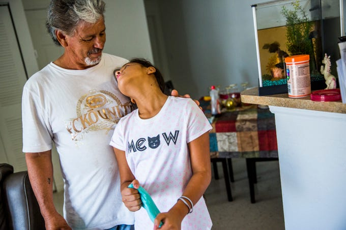 Fidencio Trevino hugs his daughter Alexia Trevino, 10, in their Immokalee apartment on Sunday, Sept. 2, 2018. The family's home was destroyed during Hurricane Irma last year and they are staying in an apartment until their home is rebuilt by several charities, including the Guadalupe Center.