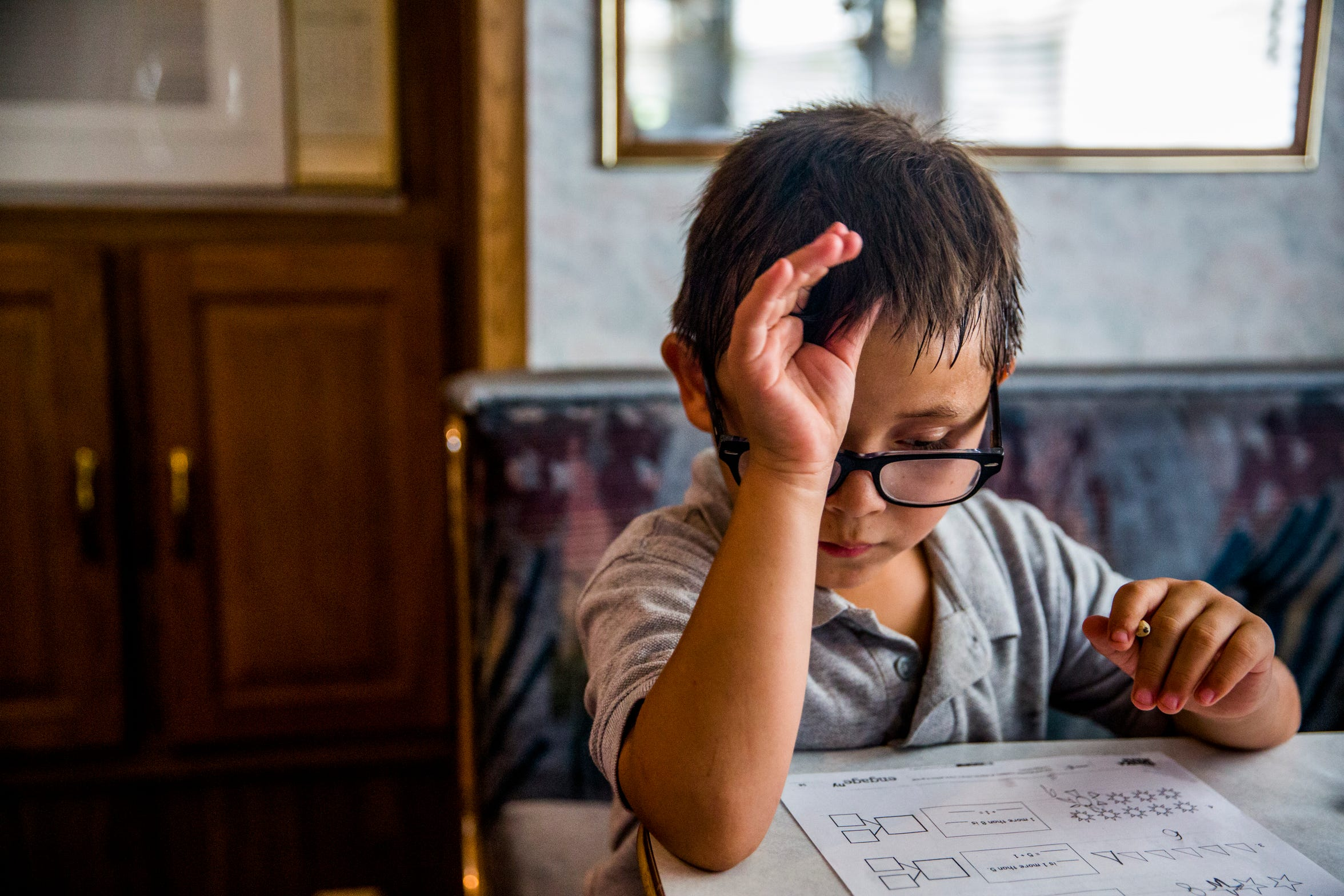 Casey Soto, 6, works on his homework in the RV he is staying in with his great-aunt in Immokalee on Wednesday, Aug. 22, 2018.