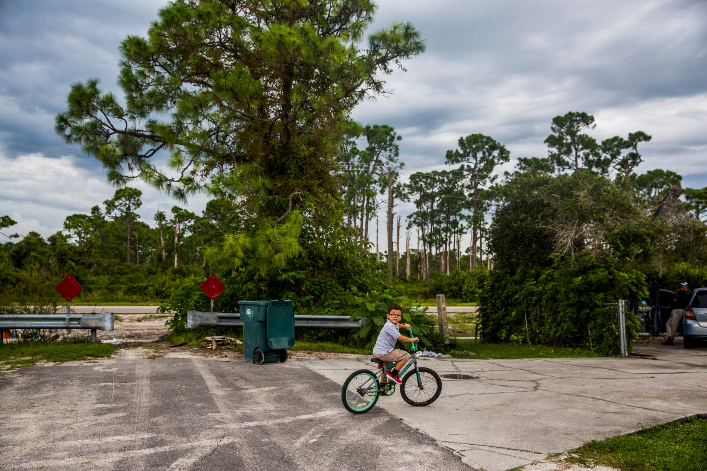 Casey Soto, 6, rides his bike in front of the plot where his Immokalee home used to be on Wednesday, Aug. 22, 2018.