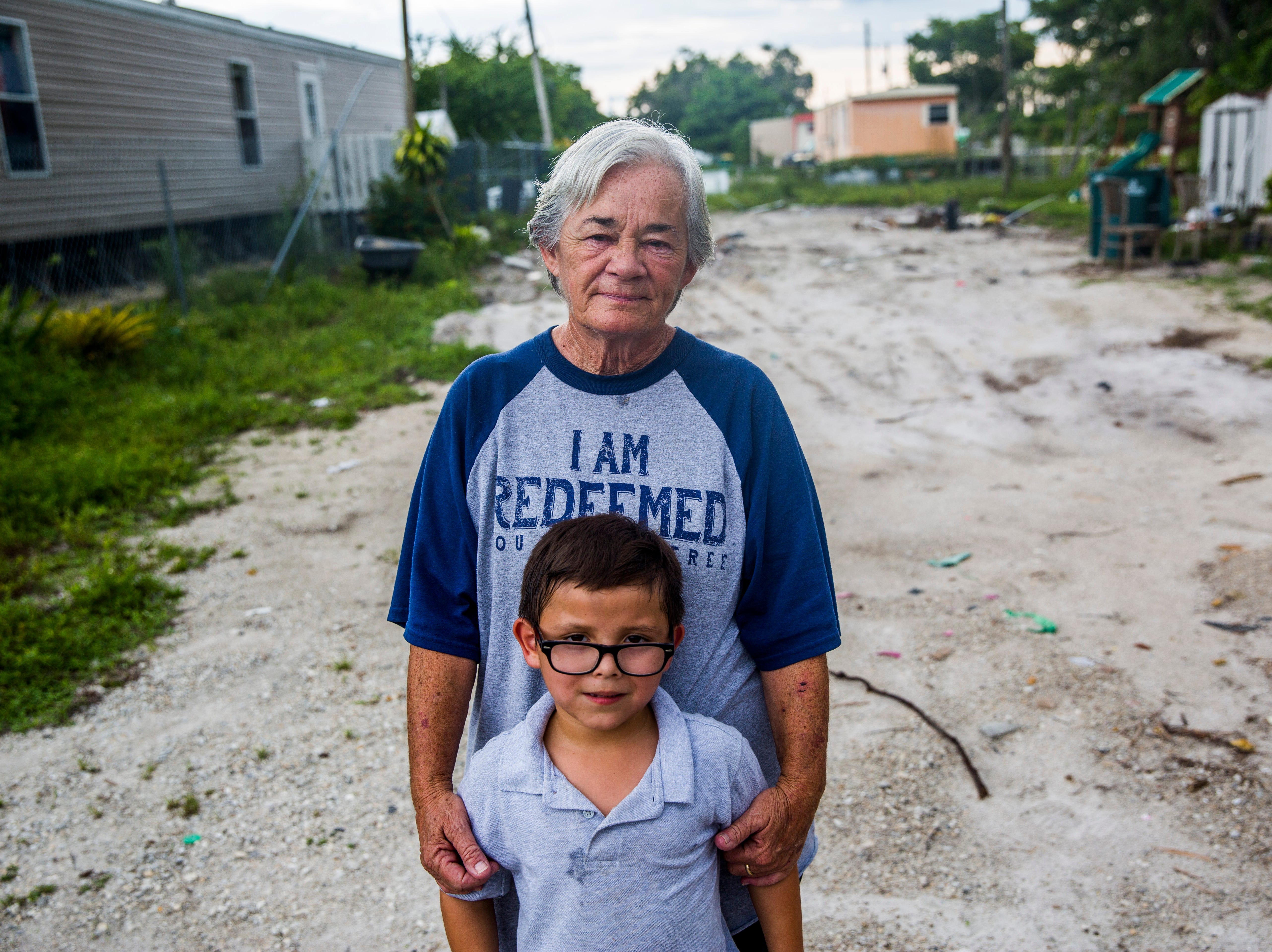 Debbie Coe, 62, and her great-nephew Casey Soto, 6, stand in front of the plot where their home used to be in Immokalee on Wednesday, Aug. 22, 2018.