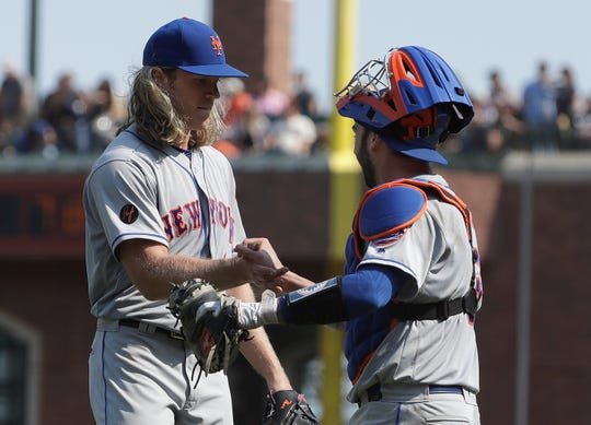 New York Mets pitcher Noah Syndergaard, left, celebrates with catcher Tomas Nido after they defeated the San Francisco Giants in a baseball game in San Francisco, Sunday, Sept. 2, 2018.