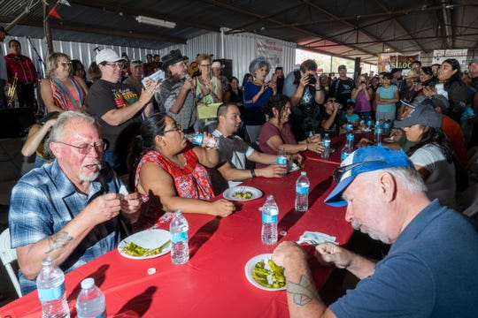 Participants frantically eat chile during the chile eating contest at the Hatch Chile Festival Saturday, Sept. 1, 2018.
