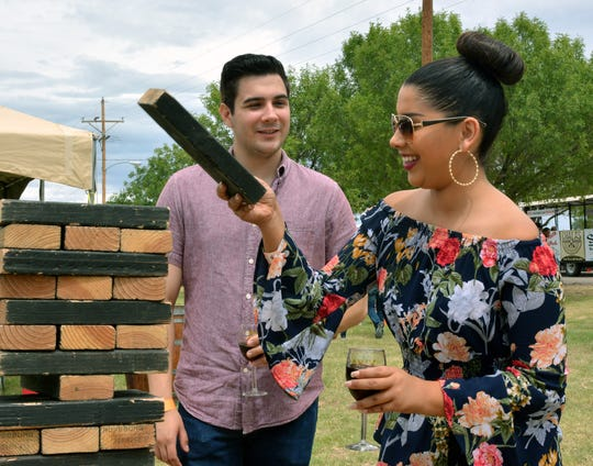 Mauricio Casillas and Diana Vasquez play a quick game of Jenga while enjoying their glasses of wine Sunday, Sept. 2, 2018, at the Las Cruces Harvest Wine Festival.