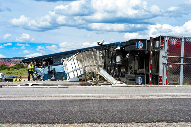 This Thursday, Aug. 30, 2018 photo shows investigators at the scene of the collision of a semitrailer that crossed the median of Interstate 40 and crashed head-on into a Greyhound bus near Thoreau, N.M. A California-based trucking company and one of its drivers were accused of negligence Friday in a pair of lawsuits as investigators sorted through the wreckage from the deadly bus crash on the New Mexico highway.