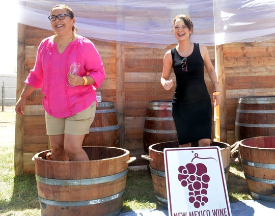 Rosa Moreno, left, and Yvonne Moreno from El Paso enjoy stomping some grapes at the Las Cruces Harvest Wine Festival on Sunday, Sept. 2, 2018.